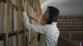 Молодой азиатский женский исследователь ища книга на книжных полках акции видеоматериалы