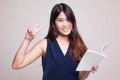 Молодой азиатский знак Виктора выставки женщины с книгой Стоковая Фотография
