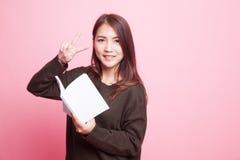 Молодой азиатский знак Виктора выставки женщины с книгой Стоковое Изображение