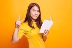 Молодой азиатский знак Виктора выставки женщины с книгой Стоковые Изображения