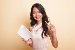 Молодой азиатский знак Виктора выставки женщины с книгой Стоковые Фото