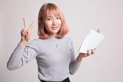 Молодой азиатский знак Виктора выставки женщины с книгой Стоковое Фото