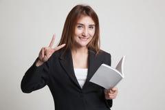 Молодой азиатский знак Виктора выставки женщины с книгой Стоковое Изображение RF