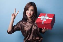 Молодой азиатский знак победы выставки женщины с подарочной коробкой Стоковая Фотография
