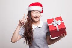 Молодой азиатский знак победы выставки женщины с подарочной коробкой Стоковые Фотографии RF