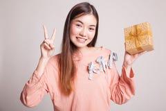 Молодой азиатский знак победы выставки женщины с подарочной коробкой Стоковые Изображения