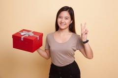 Молодой азиатский знак победы выставки женщины с подарочной коробкой Стоковая Фотография RF