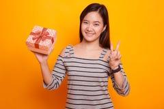 Молодой азиатский знак победы выставки женщины с подарочной коробкой Стоковое Изображение