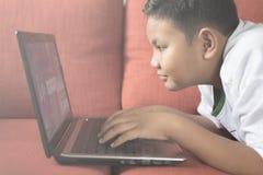 Молодой азиатский мальчик используя портативный компьютер на софе дома Стоковая Фотография RF