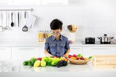 Молодой азиатский мальчик смотря к куче поддельных фруктов и овощей внутри стоковое изображение