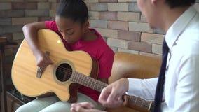Молодой азиатский мужской учитель давая урок гитары и уча как сыграть гитару к Афро-американской девушке акции видеоматериалы
