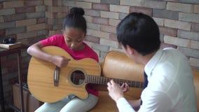 Молодой азиатский мужской учитель давая урок гитары и уча как сыграть гитару к Афро-американской девушке сток-видео