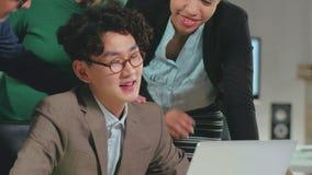 Молодой азиатский Оно-программист успешно заканчивая его работу акции видеоматериалы