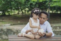 Молодой азиатский отец научить его дочери к сохраняя деньгам в копилку на лучшее будущее стоковая фотография