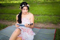 Молодой азиатский пикник женщины на луге Стоковые Фото