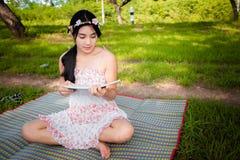 Молодой азиатский пикник женщины на луге Стоковые Изображения