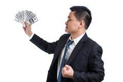 Молодой азиатский праздновать бизнесмена успешный Бизнесмен держа банкноты доллара счастливый и улыбку стоковое фото