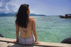 Молодой азиатский сидеть женщины счастливый на доке моря на пляже Таиланда смотря ландшафт горизонта красивый морской с enj гор Стоковая Фотография