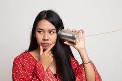 Молодой азиатский слух женщины с телефоном и мыслью жестяной коробки стоковые изображения
