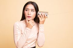 Молодой азиатский слух женщины с телефоном и мыслью жестяной коробки стоковое изображение