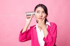 Молодой азиатский слух женщины с телефоном и мыслью жестяной коробки стоковые фото