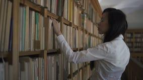 Молодой азиатский студент биолога в белой рубашке принимая старую книгу от книжных полок акции видеоматериалы