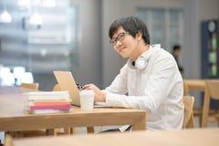 Молодой азиатский студент университета человека делая домашнюю работу стоковая фотография rf