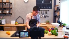 Молодой азиатский человек в видео записи кухни на камере Усмехаясь азиатский человек работая на концепции блоггера еды с фруктами