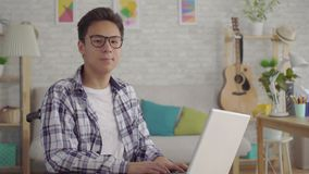 Молодой азиатский человек в стильном инвалиде стекел в кресло-коляске с работой удаленной ноутбука в живущей комнате  видеоматериал