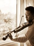 Молодой азиатский человек играя скрипку Аппаратура классической музыки Тон цвета Sepia Стоковое Фото