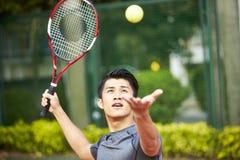Молодой азиатский человек играя теннис стоковые изображения rf