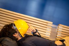 Молодой азиатский человек инженера лежа на попробованном чувстве стенда Стоковая Фотография