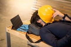 Молодой азиатский человек инженера лежа на попробованном чувстве стенда Стоковое Изображение