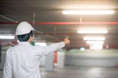 Молодой азиатский человек инженера указывая на строительную площадку Стоковое Изображение
