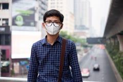 Молодой азиатский человек нося дыхательную маску N95 для защиты и для того чтобы фильтровать pm2 твердые примеси в атмосфере 5 пр стоковое фото