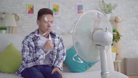 Молодой азиатский человек сидя перед работая вентилятором, концепцией жары медленного mo видеоматериал