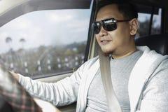 Молодой азиатский человек управляя автомобилем стоковое фото rf