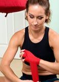Молодой активный получать женщины подготовил для тренировок оборачивая ее руки с красной лентой повязки Стоковые Изображения