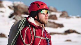 Молодой альпинист кавказского возникновения с положением бороды на наклоне снега и взглядов в горизонт и наслаждаться акции видеоматериалы