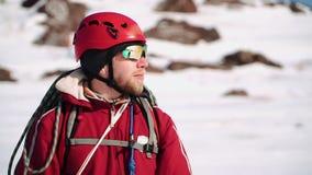 Молодой альпинист кавказского возникновения с положением бороды на наклоне и взглядах снега вокруг, стекла акции видеоматериалы