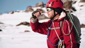 Молодой альпинист кавказского возникновения с положением бороды на наклоне снега смотрит вокруг и затеняет его глаза от сток-видео