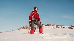 Молодой альпинист стоит поверх снежной шестерни горы полностью и наслаждается взглядом акции видеоматериалы