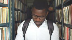 Молодой американский студент-американец выбирает книгу между полками  акции видеоматериалы