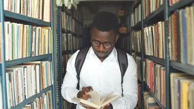 Молодой аравийский бородатый студент выбирая книгу между полками в библиотеке сток-видео