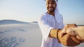 Молодой аравийский гид направляет руку ` s девушки и проводит переговор Стоковые Изображения RF
