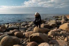 Молодой археолог на пляже валуна ища экзотические утесы на береговой  стоковая фотография rf