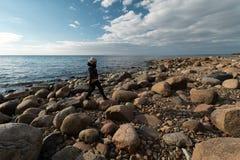 Молодой археолог на пляже валуна ища экзотические утесы на береговой  стоковые изображения