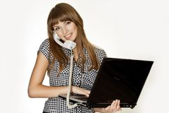 Молодой ассистент делая множественные задачи в то же время Говорить на телефоне и запись текста на ее тетради стоковое изображение rf