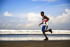 Молодой атлетический и привлекательный черный Афро-американский человек бегуна делая идущую тренировку разминки на пляже пустыни  стоковые изображения