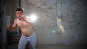 Молодой атлетический человек делая тренировки capoeira - поворачивающ вокруг и поднимая ногу сток-видео
